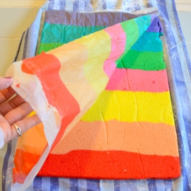 Peel wax paper off of rainbow cake